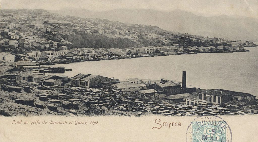 Black-and-white historic photo postcard showing houses and buildings on a hillside rising out of the sea