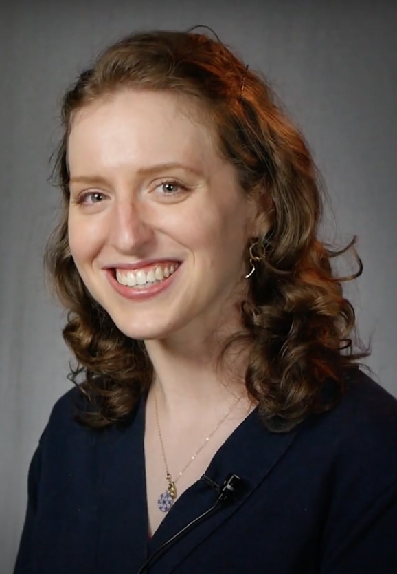 Portrait of Kendra Berry, smiling, wearing a dark blue blouse, small necklace and earrings, with a gray backdrop in the background