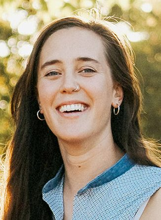 Cropped portrait of Lily Rosencrantz smiling, wearing a sleeveless blue shirt, a sunny background visible behind her