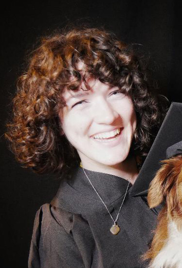 Portrait of Megan Scott smiling brightly, wearing black graduation robes and necklace, holding a small dog that is wearing a black graduation cap