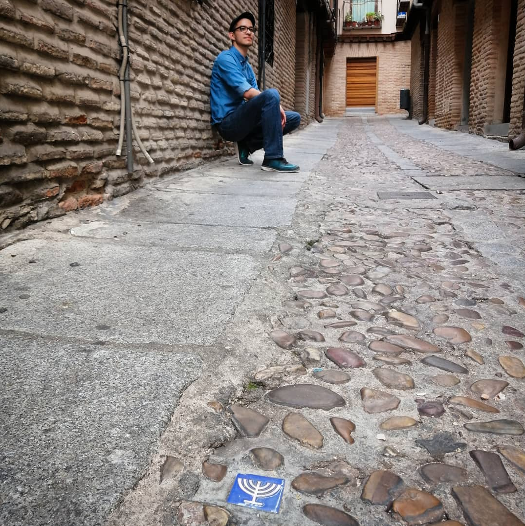 Victor in Spain. He is in the background of the image leaning against an old brick wall. The road is cobblestone. in the foreground is a blue tile with a yellow menora, the Jewish candelabra commonly seen on Hanukkah.