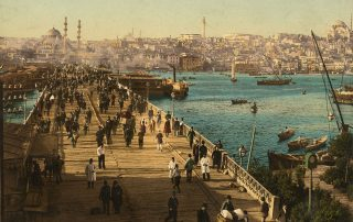 A colorized photograph shows a wide wooden bridge spanning a boat-filled river in Istanbul. Dozens of men wearing fez hats and long coats walk along the bridge. A dense cityscape and several large mosques are visible in the background.