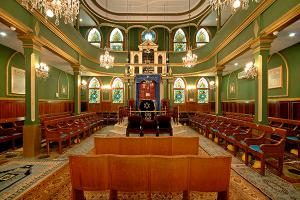 Interior of Turkish synagogue in Istanbul with green walls, a yellow carpet, and wooden pews around the perimeter. At the center is the rabbi's pulpit (bima) and in the background in the aron: the place where the Torah scrolls are kept.