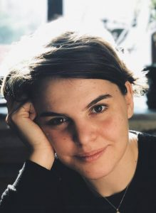 Portrait of Canan Bolel smiling, leaning her head against her hand, wearing a dark sweater, with a brick wall, window, and plants in the background