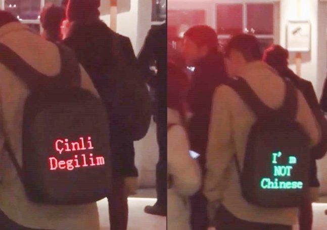"Two photos juxtaposed showing a young man in a coat wearing a light-up backpack displaying messages: ""Çinli Degilim,"" the name of a Turkish TV show, and ""I'm NOT Chinese"""