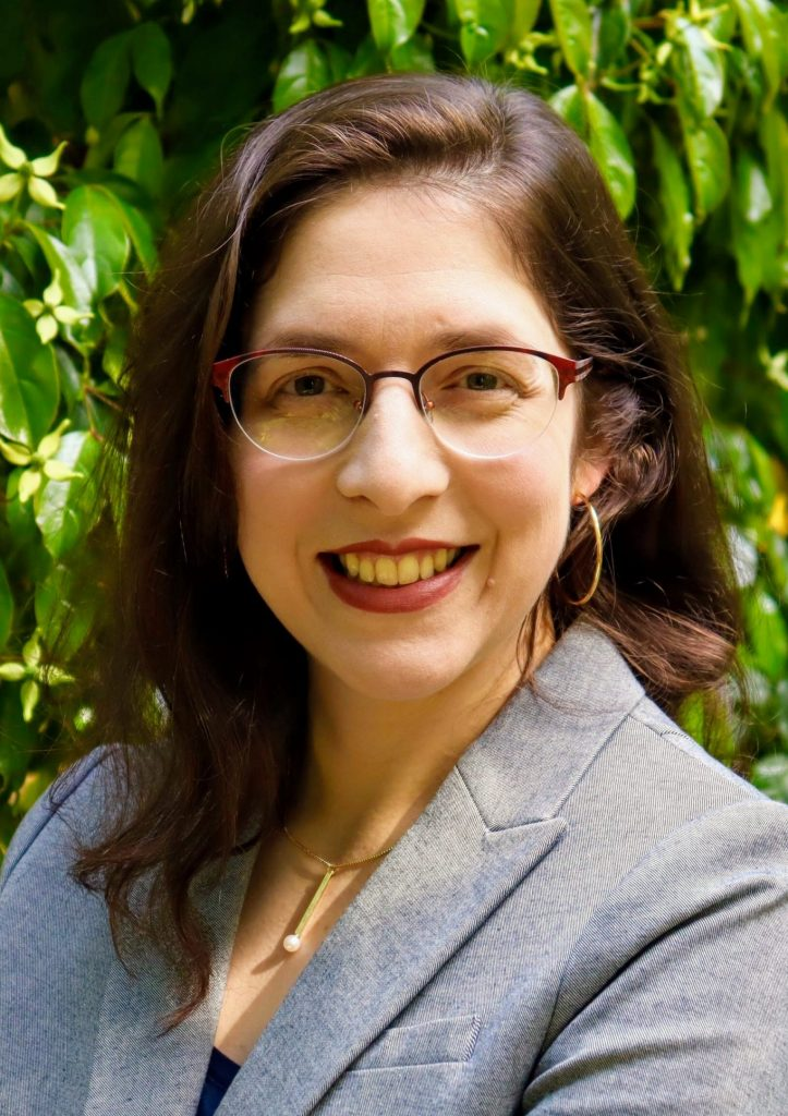 Headshot of Hannah Pressman. Pressman has brown hair and is wearing glasses, red lipstick, and a grey suit jacket. She is posted with her arms crossed, smiling, against a green leafy backdrop.