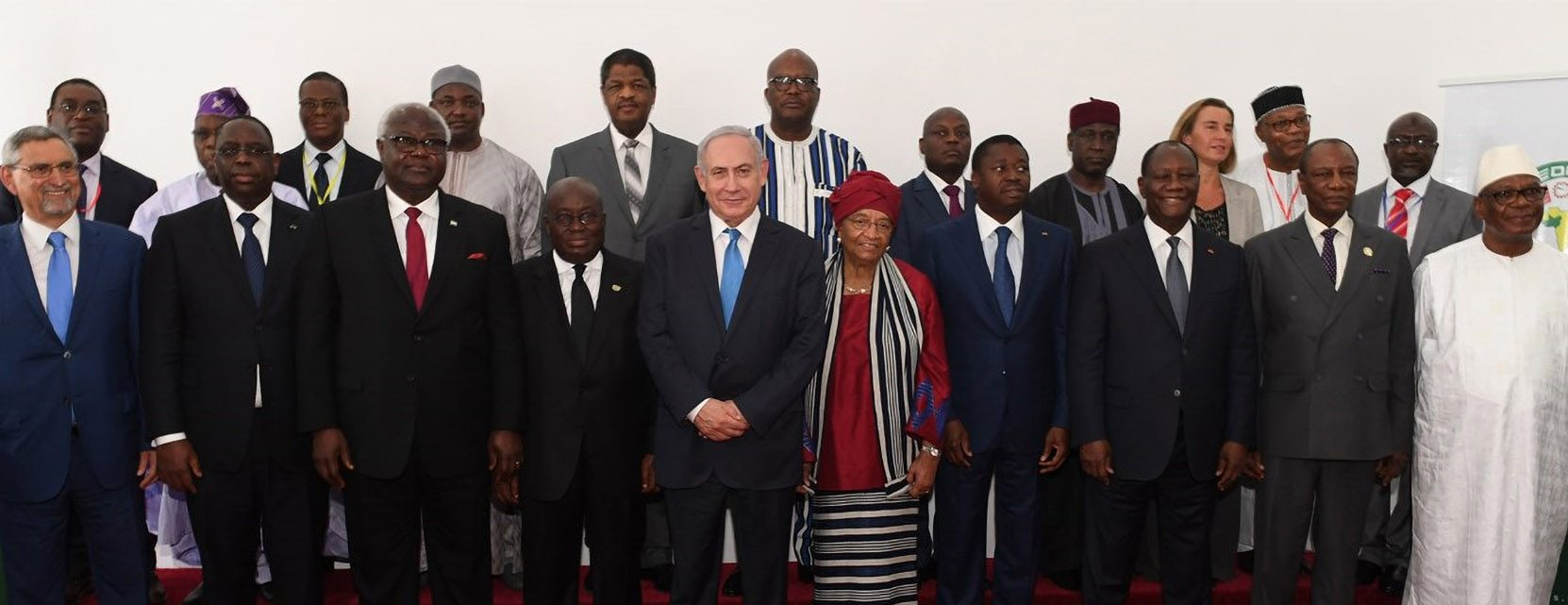 Wide-angle photograph showing Benjamin Natanyahu standing among West African leaders, all wearing formal attire, with a white wall and banners in the background
