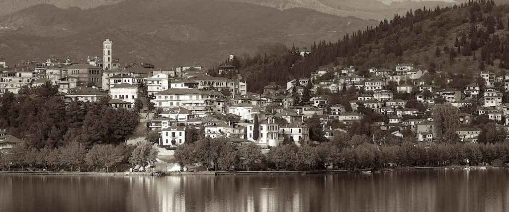 Sepia photo of Kastoria, Greece. Photo is taken from the water looking at houses dotted along a hillside. Mountains in backgrounds, homes in middle, water in image foreground.