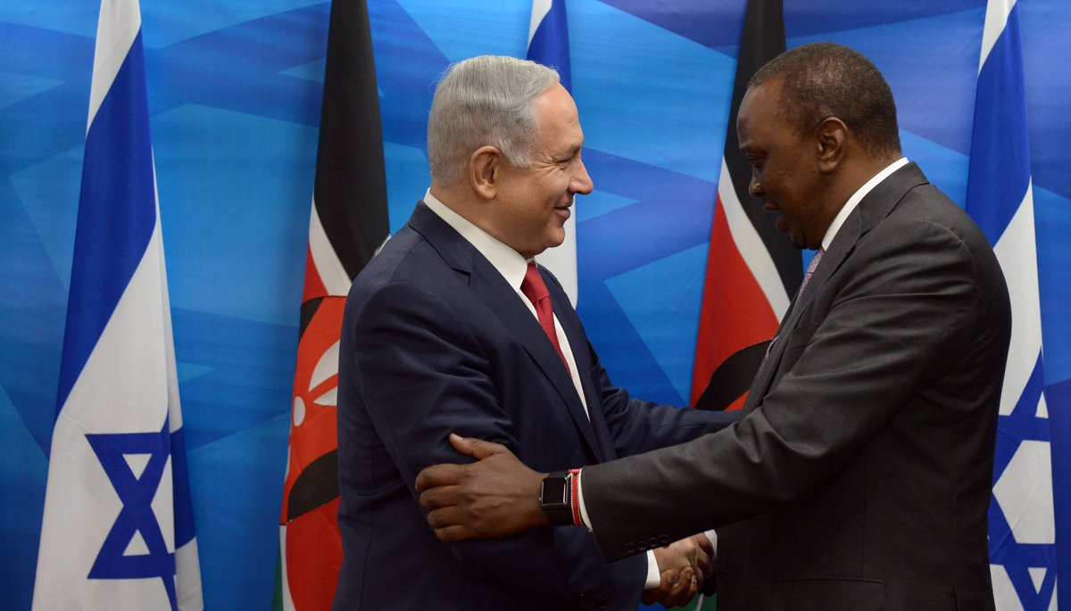 Benjamin Netanyahu and Uhuru Kenyatta shake hands and grip elbows, wearing suits and ties, with Kenyan and Israeli flags standing in the background.