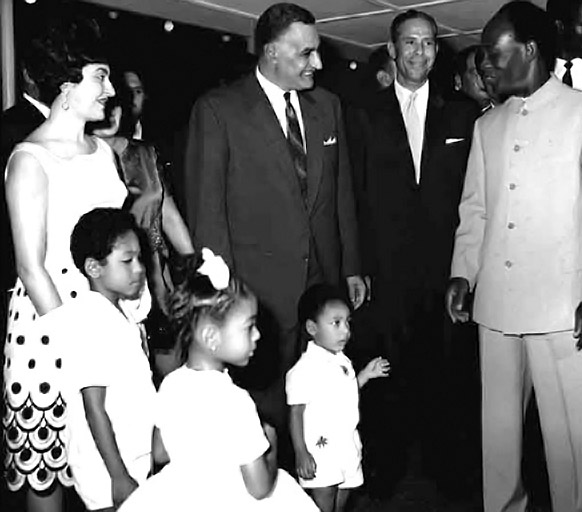 Black-and-white photograph showing Kwame Nkrumah in a formal button-up suit, smiling, standing with his family, with his wife in a sleeveless dress and three formally dressed children, all standing close to Gamal Abdel Nassar, wearing a suit and tie
