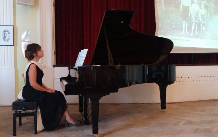 Renan Koen seated at a black grand piano. Renan is wearing a black sleeveless dress and is sitting straight-backed at the piano with hands on her lap. The room has a light brown wood floor and a burgundy wall with white trim around the baseboard and windows.