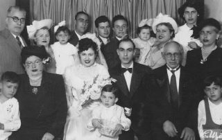 Black and white family photo of a wedding in Tekirdag, Turkey. Bride and groom seated middle with many family members around them in formal attire. Child seated on bride's lap. Background is a panel of curtains.