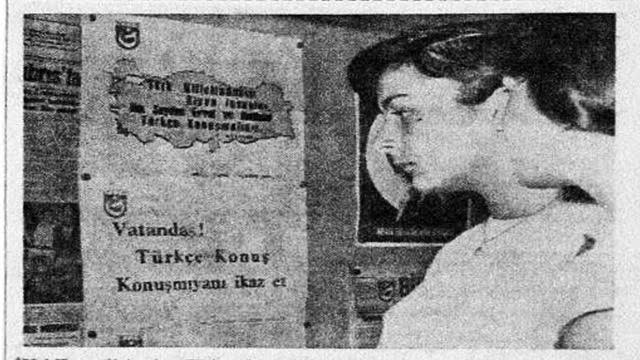 Black and white photo of two women with short hair looking at a poster from the Citizen Speak Turkish campaign. The poster is in Turkish with a grey heading. The women are wearing white dresses and are positioned at the right foreground, while the poster is at left.