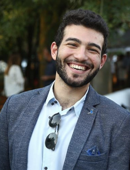 Headshot of Nesi Altaras. Wearing a grey-blue blazer with a light blue button down shirt. Sunglasses at collar. Nesi has brown hair and a beard and is smiling big with squinted eyes.