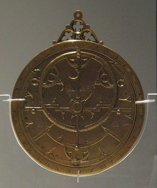 Photograph of an astrolabe, a circular tool used by medieval astronomers. The astrolabe is in the middle of the image and has several rings from exterior to interior. It has Hebrew inscriptions on the outer ring and a loop at the top, apparently to hang the tool around one's neck.