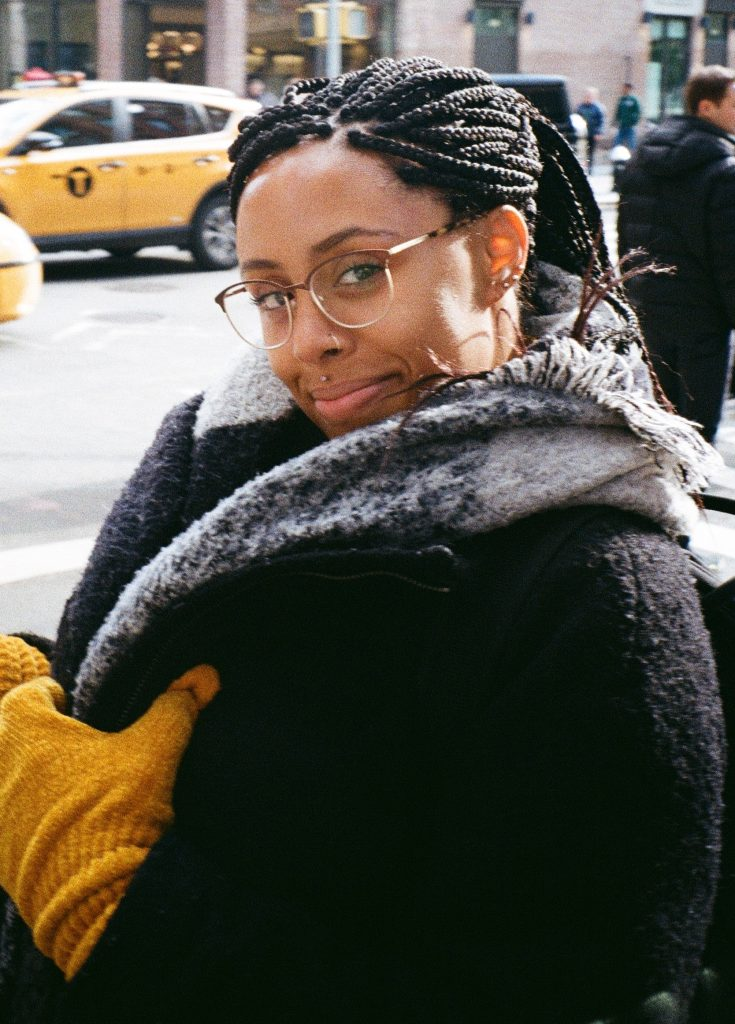 Headshot of Keah Neal-Calluccie. She is wearing a black coat, grey scarf, and yellow gloves. There is a yellow taxi cab in the background. Keah is wearing glasses. She has dark hair and darker skin. She is smiling with her mouth closed and the photo is a partial portrait.