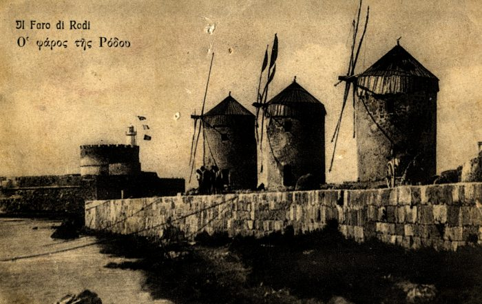 Old sepia toned postcard from Rhodes. Features three brick windmills in the foreground and a brick wall along a sea line.