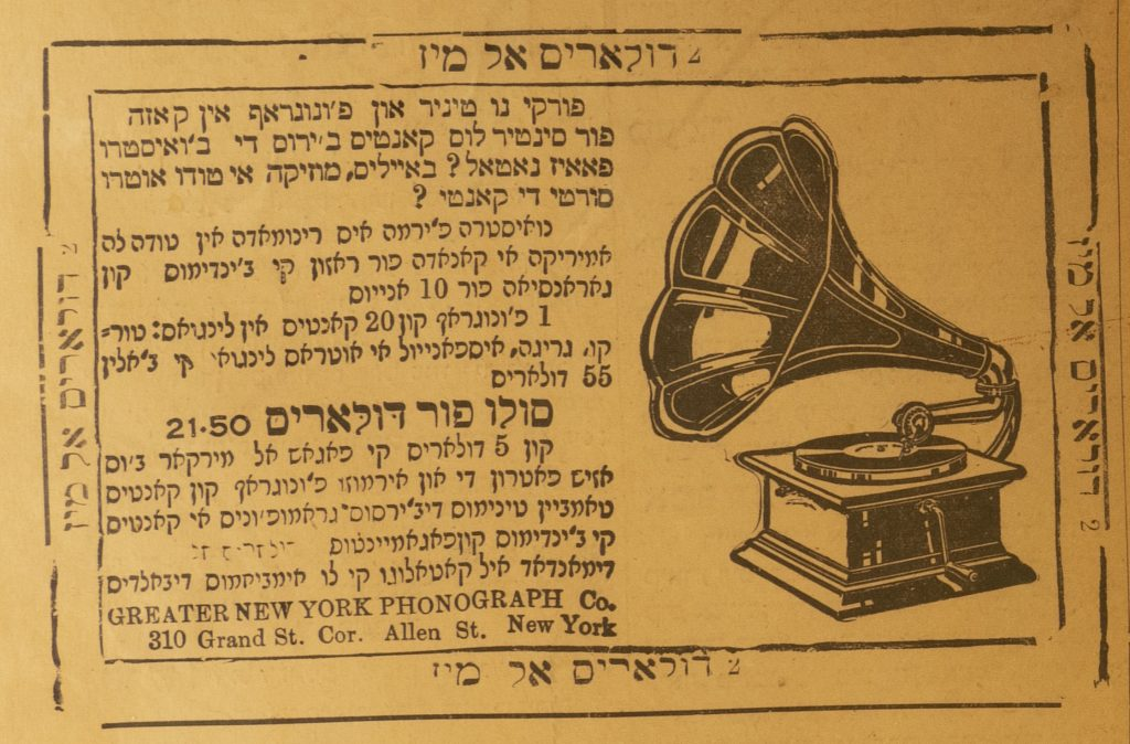 Ladino phonograph ad. Text on left side of ad, all written in Ladino in Hebrew characters. Right side of ad has a black illustration of a phonograph. The ad has a double outline border and the paper is a golden yellow color.