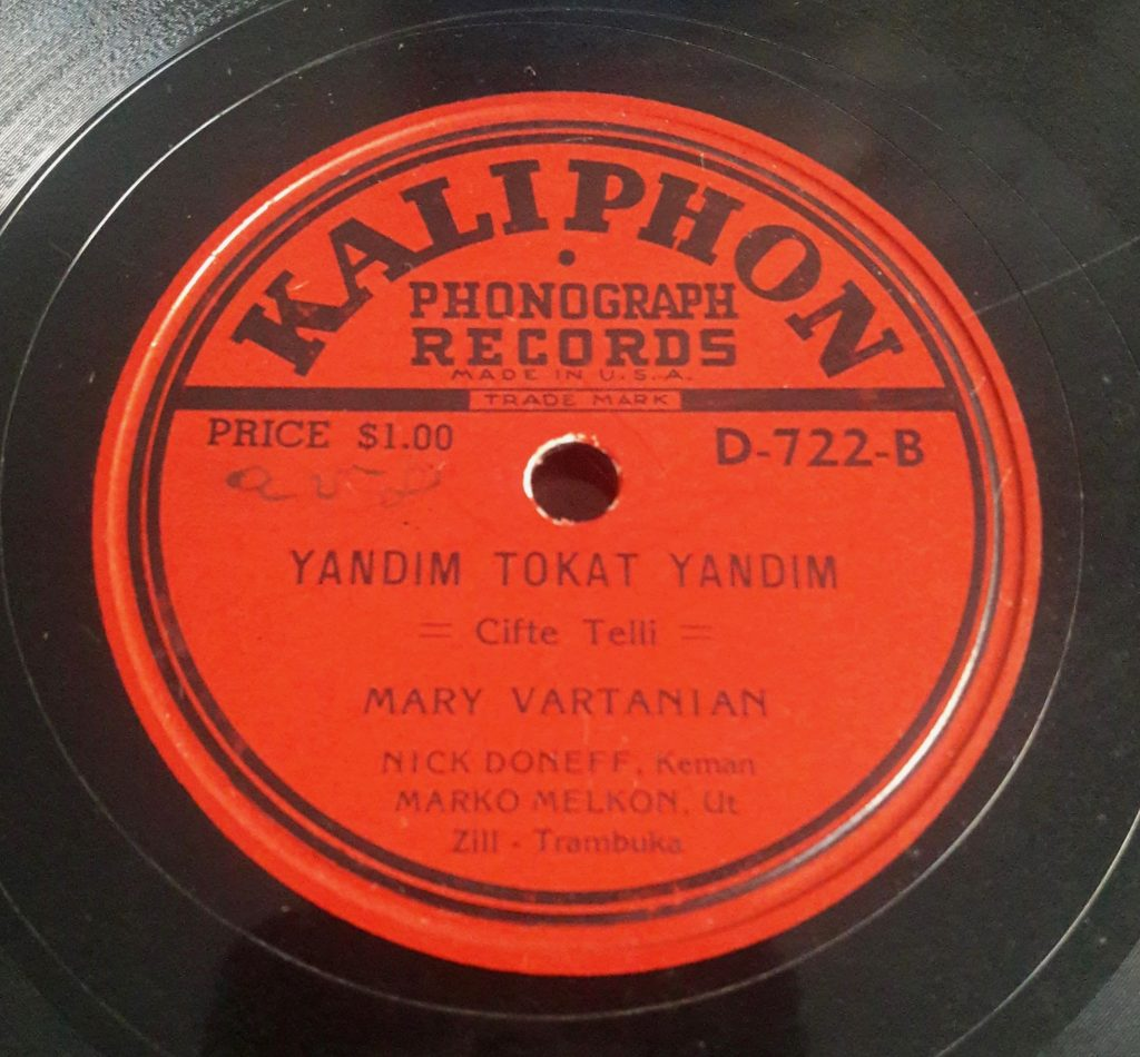Red record label against a black record. The record company is printed in black and is called KALIPHON. All other text on the lable printed in black. Hole in the middle to set record on the phonograph.