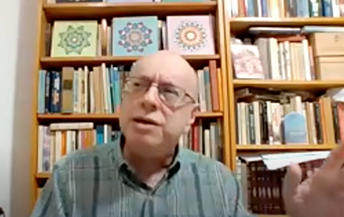 David Bunis lectures via zoom. He is wearing a light blue button down short sleeve shirt and glasses. His hands are in the midst of gesticulating. There is a bookcase behind him with colorful books and three floral images on the top shelf: one is green, one blue, the final pink.