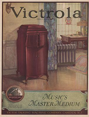 Color advertisement for a victrola. The victrola is dark brown wood and against an off white wall. To its right is a blue curtain and a metal furnace. Behind that is a window. IN the foreground of the ad is a shiny light brown floor. The world VICTROLA is printed in black at the top of the ad. At bottom is a green banner with ad text.
