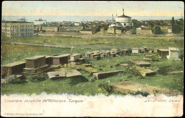 Postcard of Jewish cemetery in Salonica. Headstones are parallel to the earth. Mostly grass in foreground. Mosque and sea in background.