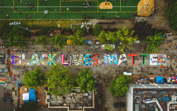 """Overhead photograph showing a colorful """"Black Lives Matter"""" mural painted on a street next to a grassy park. Photo by Kyle Kotajarvi."""