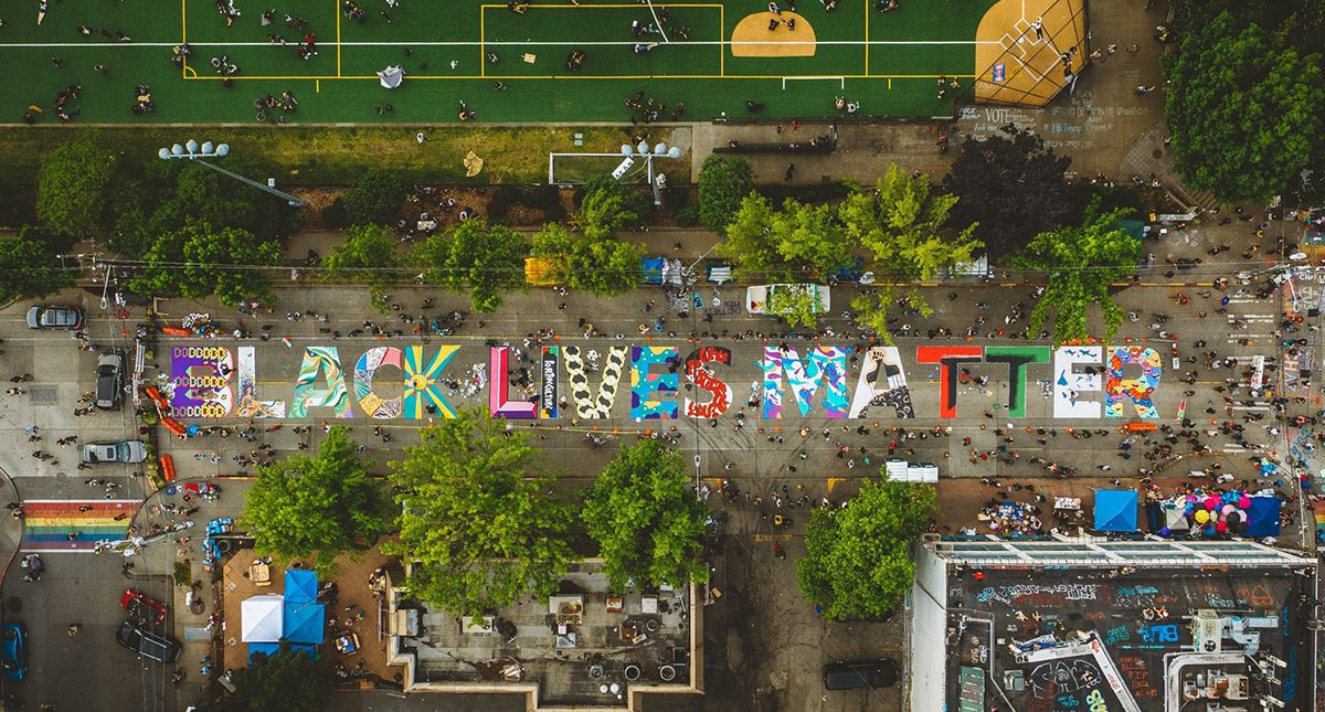 "Overhead photograph showing a colorful ""Black Lives Matter"" mural painted on a street next to a grassy park. Photo by Kyle Kotajarvi."