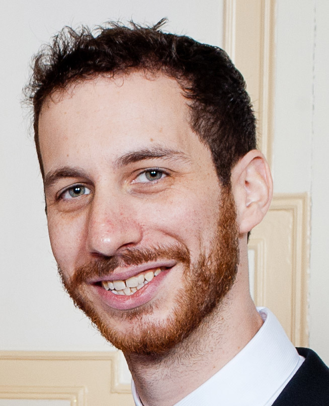 Portrait of Brendan Goldman, smiling, wearing a collared button-up white shirt and black cardigan, standing with a collegiate-looking wall in the background