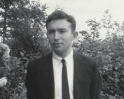 Black and white photograph shows a young Edward Alexander, wearing a button-up shirt, tie and suit jacket, standing in front of greenery, looking contemplative