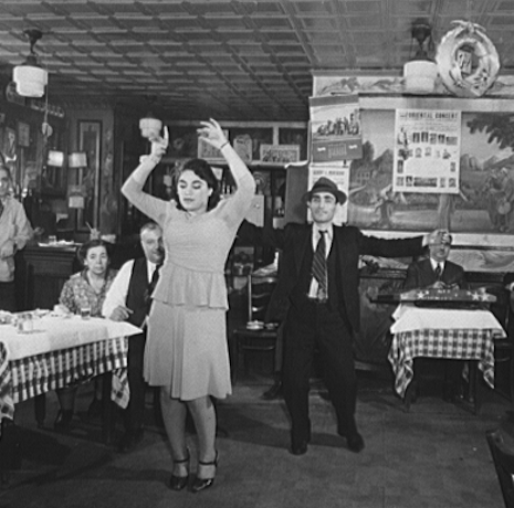 Black and white photo of a man and woman dancing in a cafe. Tables in the background have checkered table clothes. Woman is in foreground with her hands raised wearing a light colored dressed. Man is behind her in a suit and top hat with his arms outstretched. Cafe has lots of photos plastered to the walls in the background.