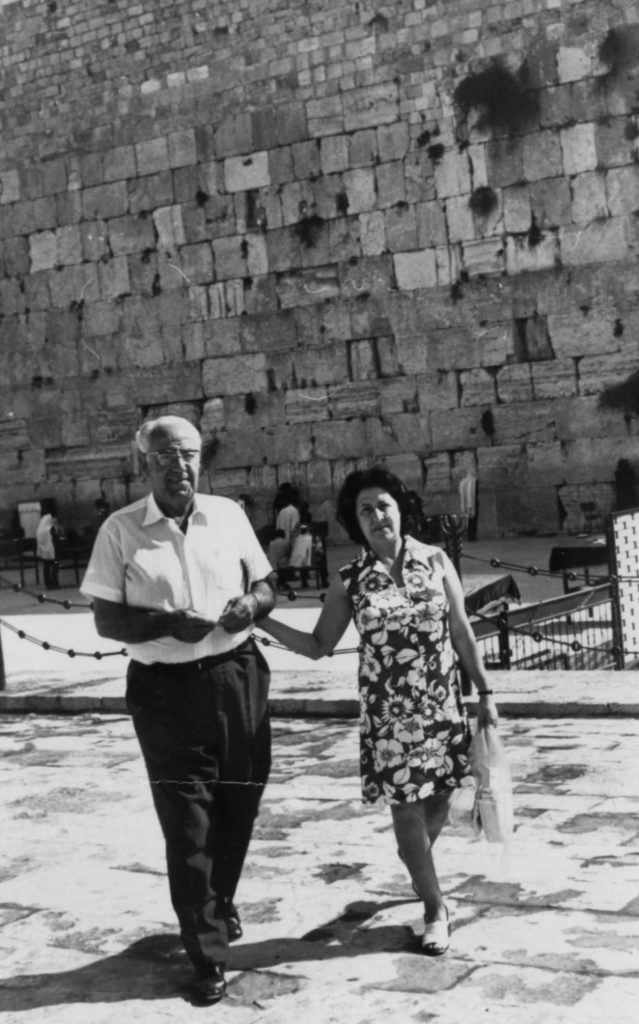 Black and white photo of a man and a woman with the Western Wall in the Jerusalem in the background. They are walking together. Woman is at left wearing a floral dress with short dark hair. Man is at left wearing dark pants and a white short sleeved shirt.
