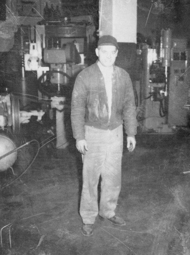 Black and white photo of Pepo Allalouf. Pepo is standing wearing a sports jacket, half zipped, and a hat, with his arms at his sides, smiling. The background looks like a factory.