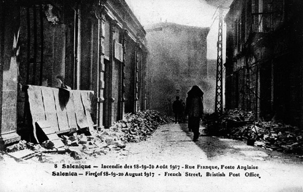 Black and white postcard showing the aftermath of the Salonika fire of 1917. Shows a burned building at left. The road recedes into the background in the middle. A person walks at the right of the frame. Smoke in background.