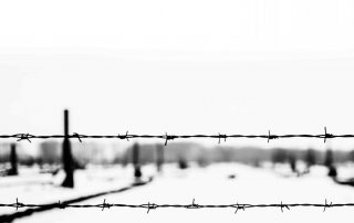 Close-up of electrified barbed wire fence of Auschwitz concentration camp. The remains of the camp on the background