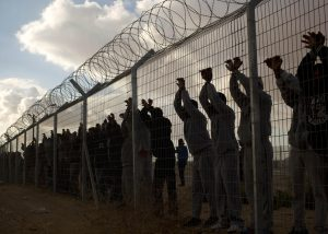Israeli prisoners protesting at a barbed wire fence