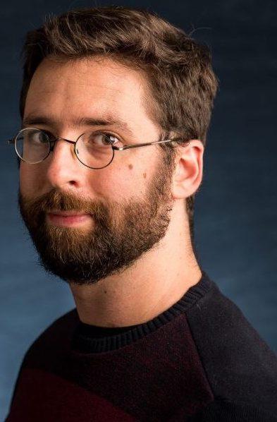 Headshot of Owen Harris wearing glasses, black sweater, against blue background.