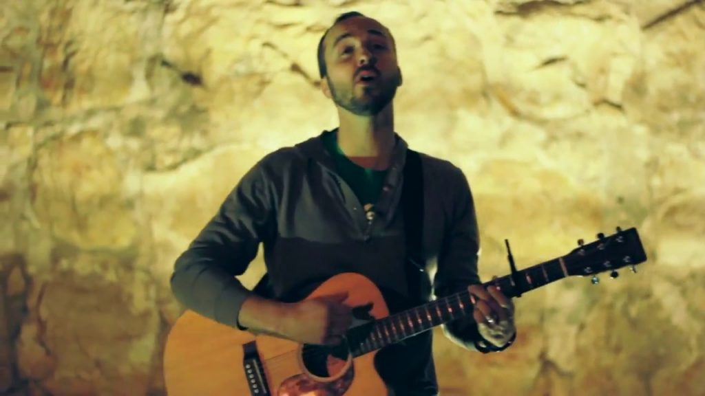 Musician Joshua Aaron plays guitar onstage