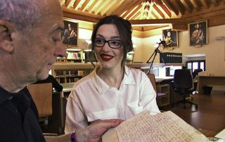 Director Joseph Lovett with Carmen Gomez Gomez, examining a 14th-century tax document in the Toledo cathedral archives, in this still from 'Children of the Inquisition.'