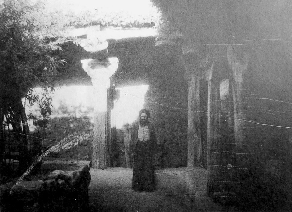 Grainy black-and-white photograph showing a man in robe and turban standing next to overgrown stone columns