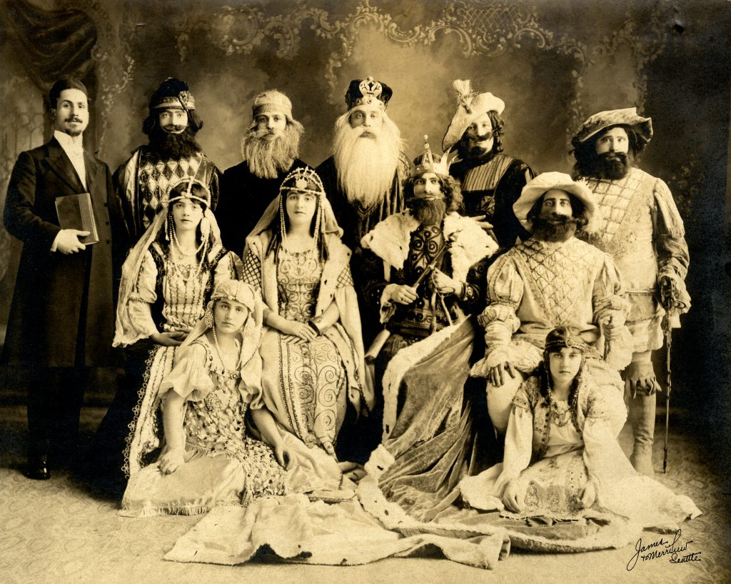 Cast portrait from Seattle Ladino theather's Queen Esther play; featured about a dozen cast members in costume; photo is sepia-toned.