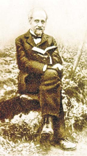 Portrait of Abraham Danon sitting on a chair with grass in the background. Photo is sepia toned, Danon wears a suit and holds an open book.