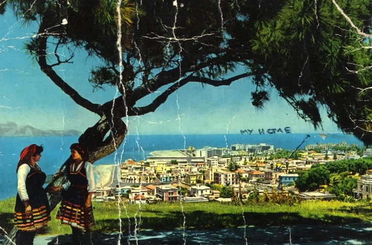 Color postcard from turn of the century Rhodes featuring a tree in the foreground and the city scape by the ocean.