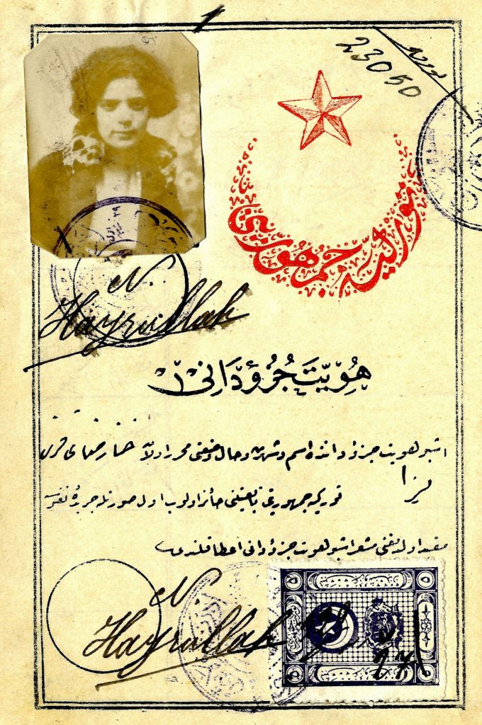 Page from Aliza Benaroya's Turkish passport with star and crescent stamp and sepia toned photo of Aliza in the top left corner.