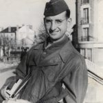 Black and white photo of David Romey smiling wearing military garb and holding books.