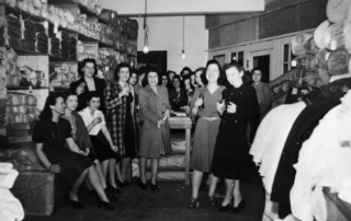 Black and white photograph of Seattle Curtain employees celebrating in stock area, Seattle, circa 1932-1941.