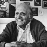 Black and white portrait of Henry Benezra wearing a button down and sweater. Framed photos in background.