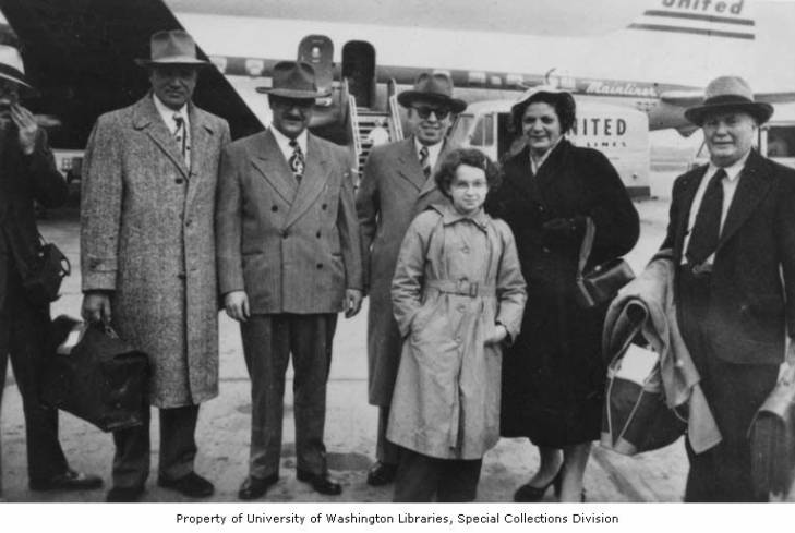 Black and white photo of Benaroya family at Sea Tac airport greeted by Sephardic community members. Air planes in background. All subjects wearing coats and many also wearing hats.
