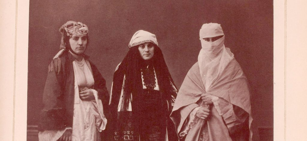 Historic sepia photographic showing women in robes and head and face coverings