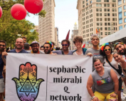 Young Sephardic Jews gather at New York's pride parade with a Sephardic Mizrahi Q Network banner.